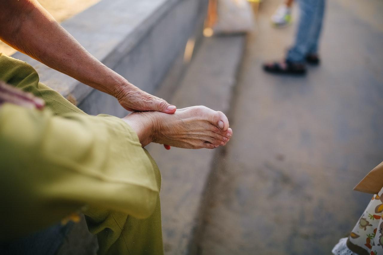 Medical Marijuana patient rubbing foot hurting from Neuropathy